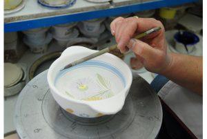 décoration d'un bol henriot Quimper par une peinteuser